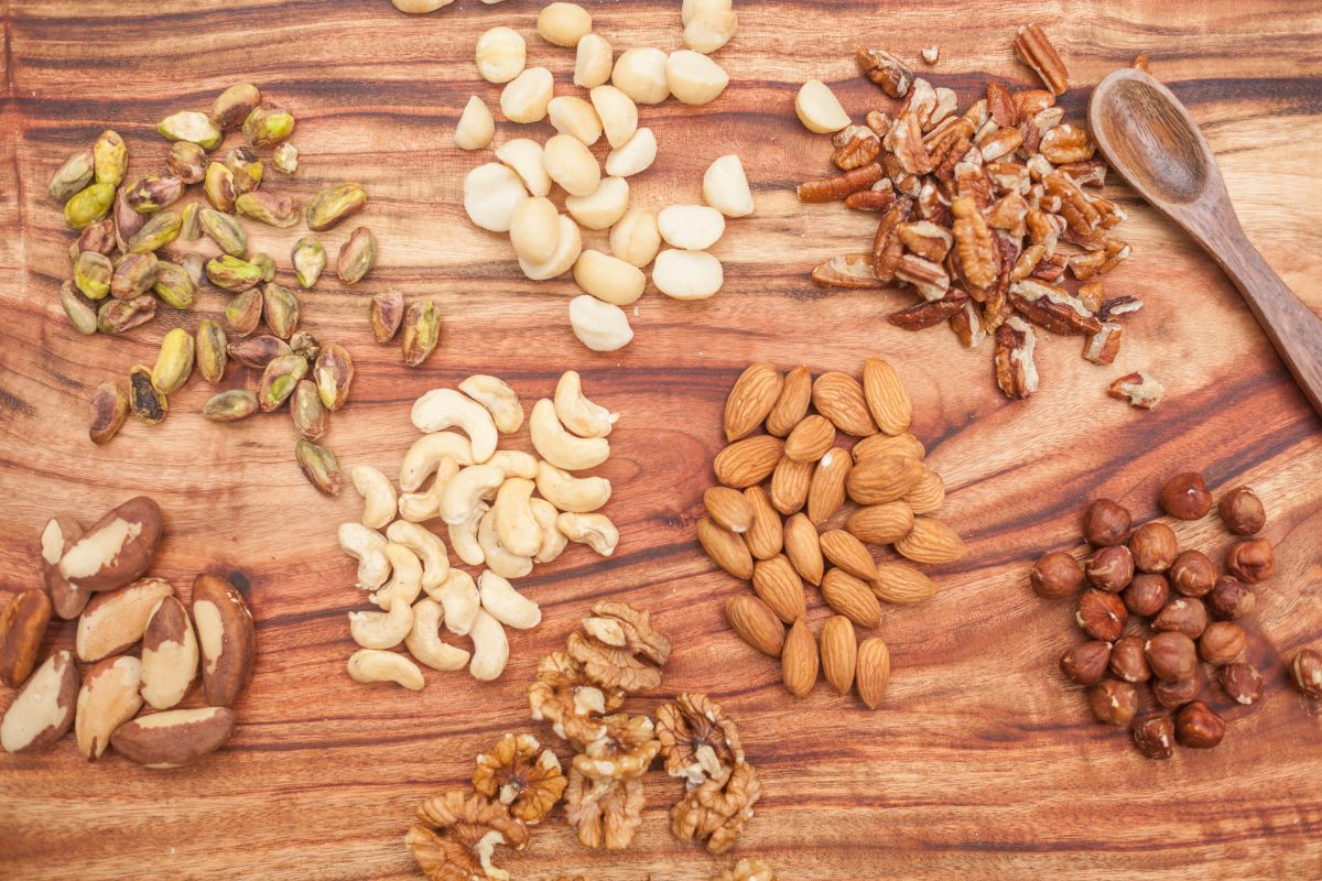 Little piles of Organic Pistachio, Macadamias, Walnuts, Pecans, Brazil nuts, Hazelnuts, Cashews and Almonds on a wooden background