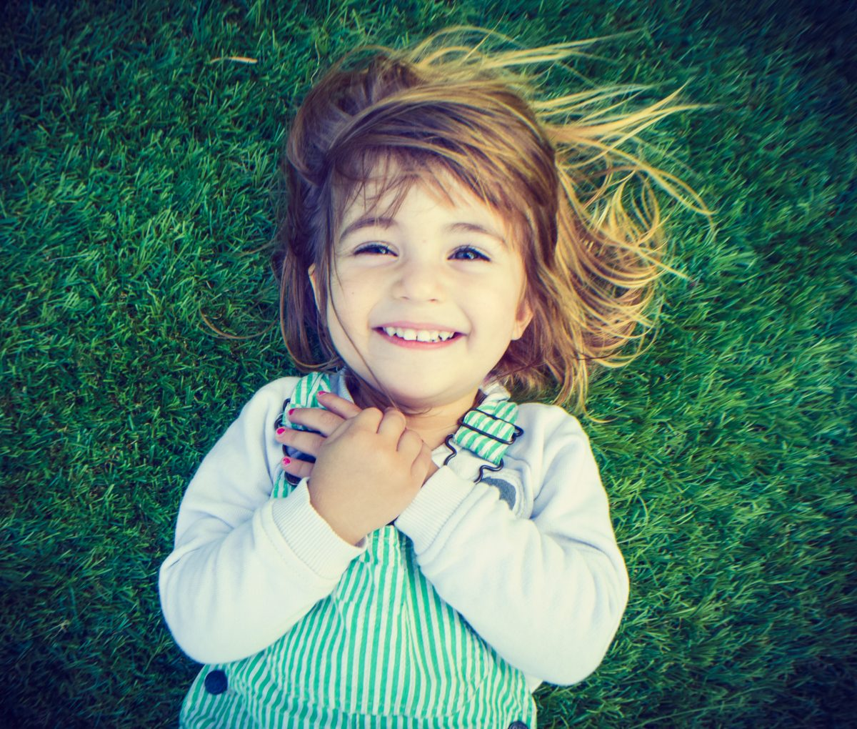Adorable little girl laying on a carpet of green grass